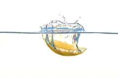 Lemon falling into water with a splash. Yellow lemon falling into water with a splash stock photo