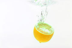 Lemon falling in water on white background Stock Photography