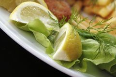 Lemon, fish and chips. Picture of lemon and lettuce on the plate royalty free stock image