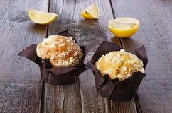 Lemon flavoured muffins on dark wooden background. Two lemon flavoured muffins and lemon quarters on a rustic dark wooden background royalty free stock photo