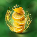 Lemon flying in air with juice splash on green Royalty Free Stock Photography