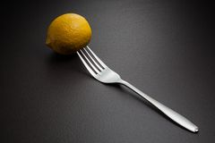 Lemon and fork on black Royalty Free Stock Photo