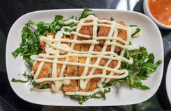 Lemon fried chicken topped with mayonnaise decorate white plate and vegetable=. Lemon fried chicken topped with mayonnaise decorate white plate and vegetable Stock Photos
