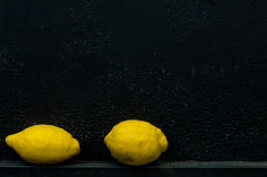 Lemon in front of rough textured black background Royalty Free Stock Photography