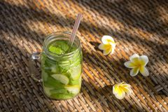 Lemon fruit Caipirinha alcoholic beverage of Brazil on wooden table. Lemon fruit Caipirinha alcoholic beverage of Brazil in glass mug on wooden table, close up Stock Photo
