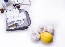 Lemon and garlic versus druga and pills on white background stock image
