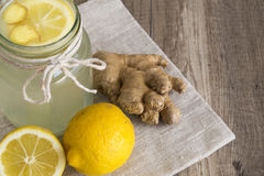 Lemon and Ginger Drink in a Jar. Lemon and ginger hot drink for detox diet. Drink in glass jar with ingredients on a napkin Royalty Free Stock Image