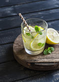Lemon, ginger and mint lemonade on a wooden rustic board. Stock Photo