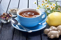 Lemon Detox Ginger Tea Cup. A blue cup with ginger lemon tea with ingredients and flowers Royalty Free Stock Photography
