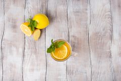 Lemon ginger tea in glass with mint and honey on a white background. Top view. royalty free stock image