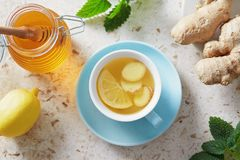 Lemon and ginger tea with honey. Cup of hot honey lemon tea with fresh ginger root stock photography