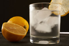 Lemon and a glass of ice water Royalty Free Stock Photos