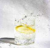Lemon in glass. Splash frozen. Lemon in glass with water. Splash frozen Stock Images