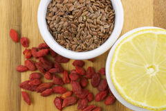 Lemon, goji berries and linseeds. On wooden background Royalty Free Stock Images