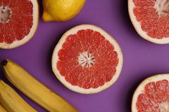 Lemon, grapefruits and bananas on bright lilac background Stock Photography