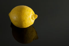 Lemon on a gray background. Ripe lemon on a gray reflective background Stock Images