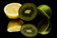 A lemon, green lemon and a kiwi,  Royalty Free Stock Photos