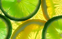 Lemon and green lime overlapped slices close-up background. Royalty Free Stock Photography
