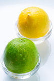 Lemon and green lime with water drops in the glass bowls stock photos