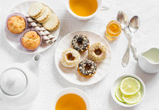 Lemon green tea and sweets - banana muffins, cookies with caramel and nuts, donuts with chocolate and lemon glaze, tea set on whit Royalty Free Stock Photos