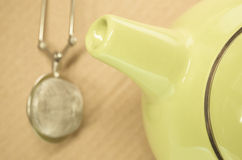 Lemon green teapot spout and background strainer Stock Image