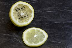 Lemon half with nutritional label. Sliced fresh lemon with nutritional facts label on black royalty free stock image