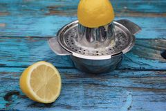 Lemon Halves Being Juiced in Metal Juicer royalty free stock photos