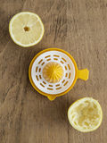 Lemon halves and lemon squeezer. On wooden background royalty free stock images