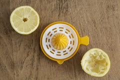 Lemon halves and lemon squeezer Stock Images