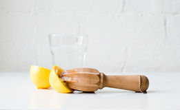 Lemon halves with reamer and water. Lemon halves and citrus reamer in front of glass of water on white table against rustic white brick wall stock image