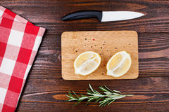 Lemon halves on wooden table. Lemon halves with spices, lying on wooden board on wooden table with rosemary, checkered napkin and white knife Stock Images
