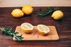 Lemon halves on wooden table. Lemon halves with spices, lying on wooden board on wooden table with rosemary and other lemons Stock Photo