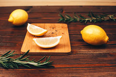 Lemon halves on wooden table. Lemon halves with spices, lying on wooden board on wooden table with rosemary and other lemons Stock Image