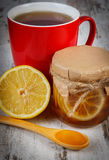 Lemon with honey and cup of tea on wooden table, healthy nutrition Stock Image