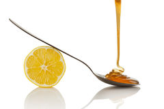 Lemon and Honey. Lemon slice and honey flowing on spoon Stock Image