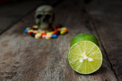 Lemon and human skull in the pile of drugs. Royalty Free Stock Images