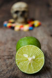 Lemon and human skull in the pile of drugs. Royalty Free Stock Photos
