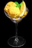 Lemon ice cream with piece of lemon in glass cup on black backgr Royalty Free Stock Photos