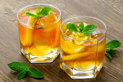 Lemon ice tea on brown wooden table with lemons Royalty Free Stock Images