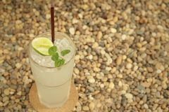 Lemon juice in a glass on a background of rock. Royalty Free Stock Image