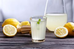 Lemon juice in glass and pitcher. On wooden table Royalty Free Stock Photos