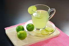Lemon juice, Lime juice and lime on black wooden table. Royalty Free Stock Photos