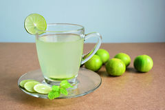 Lemon juice, Lime juice and limes on wooden table. Royalty Free Stock Photo