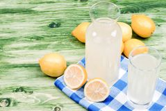 Lemon juice and typical yellow sliced lemon on a green chalkboar Royalty Free Stock Photos