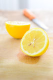 Lemon with kitchen knife on cutting board Royalty Free Stock Photo