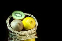 Lemon, kiwi and basket. Stock Photos