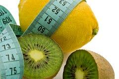 Lemon, kiwi and blue measuring tape. Lemon and kiwi fruits with blue measuring tape isolated on white background Stock Photos