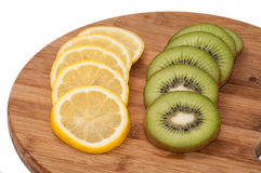 Lemon and kiwi fruit sliced on a wooden board Royalty Free Stock Photo