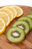 Lemon and kiwi fruit sliced on a wooden board Stock Image
