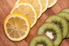 Lemon and kiwi fruit sliced on a wooden board Royalty Free Stock Photography